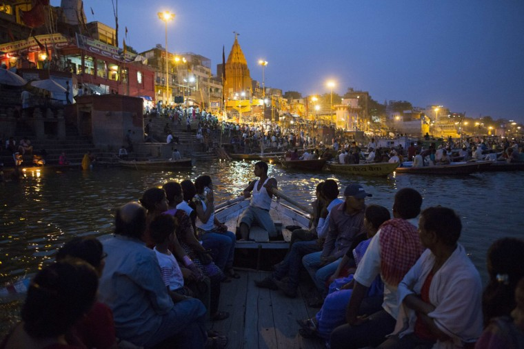 "Hindu devotees travel past holy ghats on the banks of the river Ganges in Varanasi, in the northern Indian state of Uttar Pradesh, June 16, 2014. The city of Varanasi, on the banks of the River Ganges, is widely considered Hinduism's holiest city and many Hindus believe that dying there and having their remains scattered in the Ganges allows their soul to escape a cycle of death and rebirth, attaining ""moksha"" or salvation. ""Mukti Bhavan"" or ""Salvation House"", is a charity-run hostel that caters for people who wish to come to Varanasi to die. Guests can normally stay up to two weeks after which, if they haven't yet passed away, they are gently asked to leave. Picture taken June 16, 2014. (Danish Siddiqui/Reuters)"