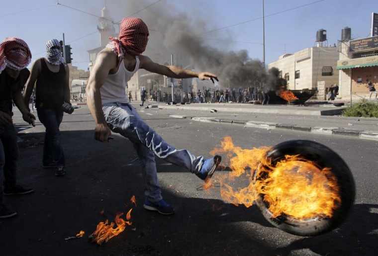 A Palestinian kicks a tire after setting it ablaze during clashes with Israeli police in Shuafat, an Arab suburb of Jerusalem July 2, 2014. The discovery of a body in a Jerusalem forest on Wednesday raised suspicions that a missing Palestinian youth had been killed by Israelis avenging the deaths of three abducted Jewish teens. Rock-throwing Palestinians clashed with Israeli forces in Jerusalem after the news, but no serious injuries were reported. (Ammar Awad/Reuters)