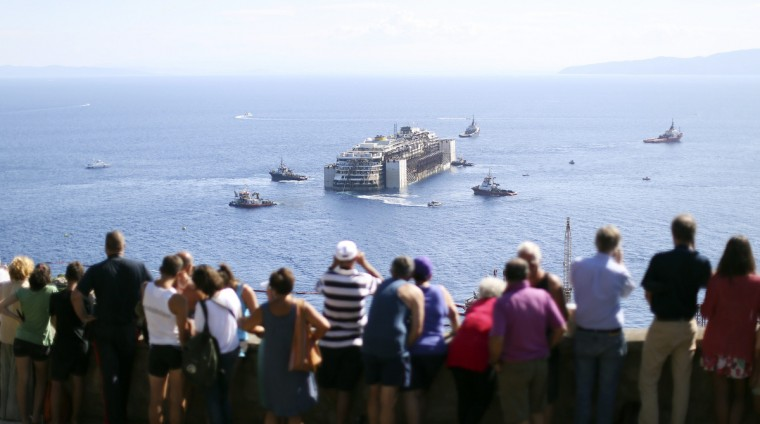 People watch the cruise liner Costa Concordia moving anticlockwise during the refloat operation maneuvers at Giglio Island July 23, 2014. Maneuvers began early on Wednesday to remove the rusty hulk of the Costa Concordia cruise liner from the Italian island where it struck rocks and capsized two years ago, killing 32 people. A convoy of 14 vessels, led by the tug boat Blizzard, will start to tow the Concordia later on Wednesday to a port near Genoa in northern Italy where it is due to arrive on Sunday, before being broken up for scrap. (Alessandro Bianchi/Reuters)