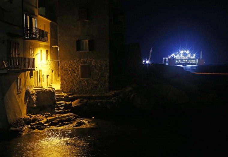 The Costa Concordia (R) cruise liner is seen at Giglio harbour at Giglio Island, early July 18, 2014. Preparations to tow away the Costa Concordia continued on the Italian island of Giglio on Thursday, with engineers connecting the last chains and cables to the sponsons, the large metal boxes attached to the wreck. The wrecked luxury liner is expected be towed away next Monday from the Italian island where it sank two and half years ago, killing 32 people.  || PHOTO CREDIT: ALESSANDRO BIANCHI  - REUTERS