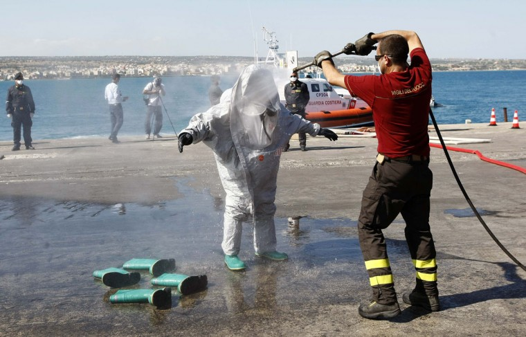 A firefighter cleans his colleague after he disembarked from a boat, on which some 30 bodies were found, after the Italian Navy towed it into the Sicilian harbour of Pozzallo July 1, 2014. As many as 30 corpses were found on the boat packed with migrants off the coast of Sicily. Italy's navy towed the boat into the Sicilian harbour of Pozzallo on Tuesday after rescuing thousands of people trying to cross from North Africa over the weekend. The dead are believed to have either suffocated on this overcrowded boat or drowned. (REUTERS/Antonio Parrinello)