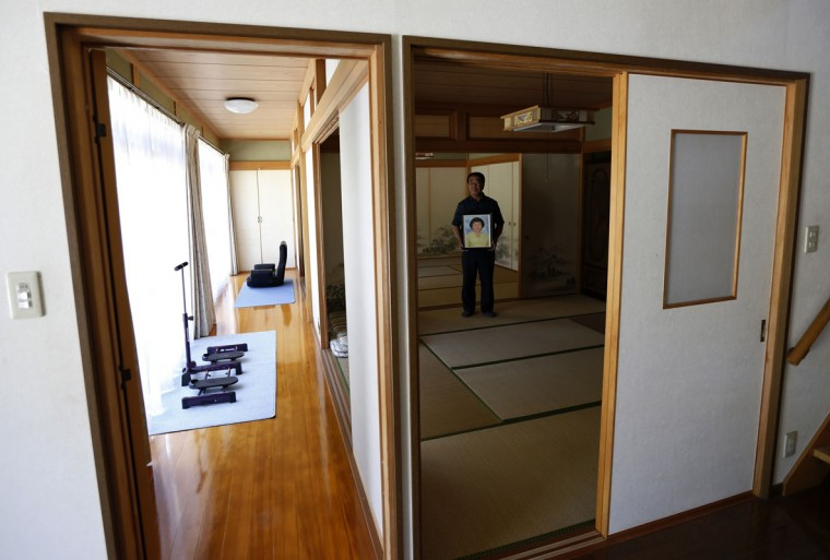Mikio Watanabe holds a portrait of his late wife Hamako as he poses for a photo at his home at Yamakiya district in Kawamata town, Fukushima prefecture June 23, 2014. In July 2011, nearly four months after the massive earthquake and tsunami that triggered a series of catastrophic failures at the Fukushima Daiichi nuclear plant, Hamako Watanabe returned to her still-radioactive hilltop home, doused herself in kerosene and set herself on fire. She left no suicide note, but her husband Mikio, who discovered her charred body, says plant operator Tokyo Electric is directly responsible. A district court in Fukushima is expected to rule in late August on Watanabe's lawsuit, which Tokyo Electric (Tepco) is contesting. Watanabe's house is still in an exclusion zone, where traffic is restricted to former residents and decontamination crews and he regularly commutes to maintain the empty home. Picture taken June 23, 2014. REUTERS/Issei Kato