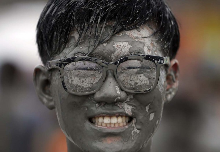 A tourist poses for photographs as he plays in the mud during the Boryeong Mud Festival at Daecheon beach in Boryeong July 18. About 2 to 3 million domestic and international tourists visit the beach during the annual mud festival, according to the festival organisers.   || PHOTO CREDIT: KIM HONG-JI  - REUTERS