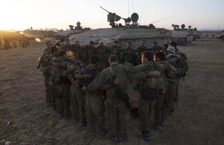 Israeli soldiers from the Golani Brigade stand in a circle at a staging area before entering Gaza from Israel July 30, 2014. Israeli fire killed at least 43 Palestinians in the Gaza Strip early on Wednesday as the Jewish state said it targeted Islamist militants at dozens of sites across the coastal enclave, while Egyptian mediators prepared a revised ceasefire proposal. (Baz Ratner/Reuters photo)