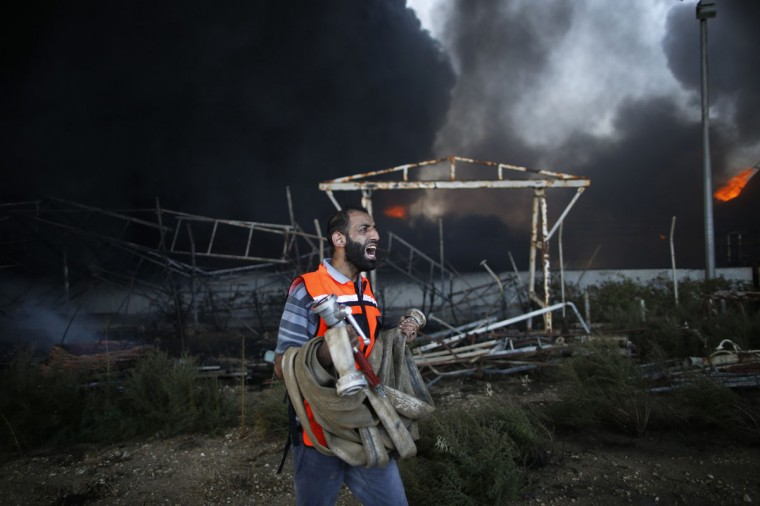 A Palestinian firefighter reacts as he tries to put out a fire at Gaza's main power plant, which witnesses said was hit in Israeli shelling, in the central Gaza Strip July 29, 2014. Israeli tank fire hit the fuel depot of the Gaza Strip's only power plant on Tuesday, witnesses said, cutting electricity to Gaza City and many other parts of the Palestinian enclave of 1.8 million people.An Israeli military spokeswoman had no immediate comment and said she was checking the report. Israel launched its Gaza offensive on July 8, saying its aim was to halt rocket attacks by Hamas and its allies. (REUTERS/Mohammed Salem)