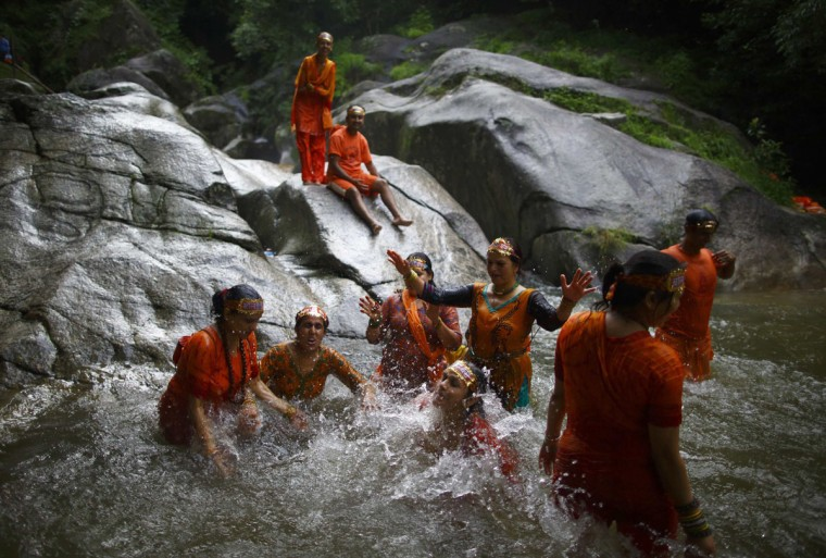 "Hindu devotees take a dip at the Bagmati River as they participate in the ""Bol Bom"" (Say Shiva) pilgrimage in Kathmandu July 21, 2014. The faithful, chanting the name of Lord Shiva, run about 15 km (9 miles) barefooted toward Pashupatinath temple seeking good health, wealth and happiness. (REUTERS/Navesh Chitrakar)"