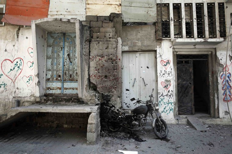 A charred motorcycle stands beside buildings damaged by shrapnel in the Shejaia neighborhood, which was heavily shelled by Israel during fighting, in Gaza City July 20, 2014. At least 50 Palestinians were killed on Sunday by Israeli shelling in a Gaza neighborhood, where bodies were strewn in the street and thousands fled for shelter to a hospital packed with wounded, witnesses and health officials said. Militants kept up their rocket fire on Israel, with no sign of a diplomatic breakthrough toward a ceasefire in sight. (Finbarr O'Reilly/Reuters)