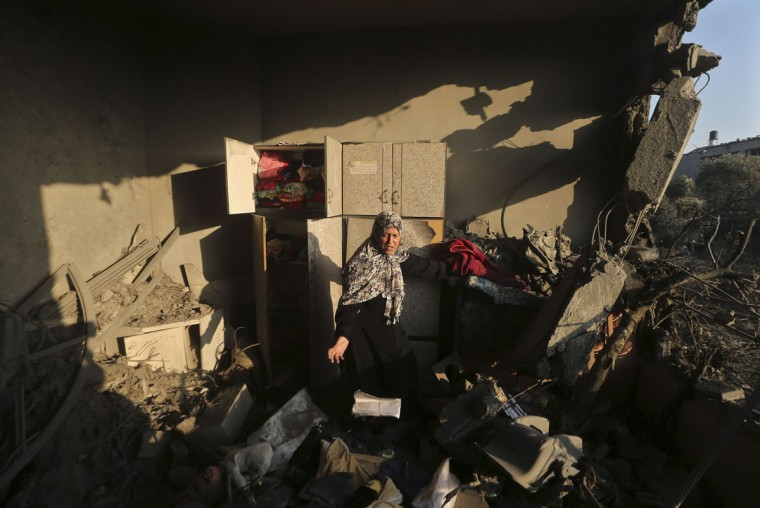 "A Palestinian woman inspects her house which police said was damaged in an Israeli air strike on a neighbouring house in Gaza City July 8, 2014. Israel launched an aerial offensive in the Gaza Strip on Tuesday, bombing more than 30 targets including homes and calling it part of a campaign named ""Operation Protective Edge"" targeting Hamas Islamist militants firing rockets at the Jewish state. The military urged Israelis within a 40-km (24-mile) radius of the southern coastal territory to stay within reach of protected areas and ordered summer camps shut as a precaution against rocket fire. Palestinian officials said Israel bombed more than 30 targets in little more than an hour before dawn, including two homes in southern Gaza, one of which was identified by a neighbour as belonging to a Hamas member. (REUTERS/Mohammed Salem)"