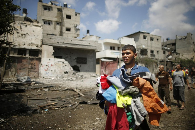 A Palestinian carries his clothes in the Shejaia neighborhood which was heavily shelled by Israel during fighting in Gaza City July 20, 2014. At least 50 Palestinians were killed on Sunday by Israeli shelling in the Gaza neighborhood, where bodies were strewn in the street and thousands fled for shelter to a hospital packed with wounded, witnesses and health officials said. Militants kept up their rocket fire on Israel, with no sign of a diplomatic breakthrough toward a ceasefire in sight. (Mohammed Salem/Reuters)