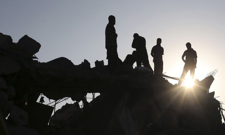 Palestinians stand amongst the rubble of a house which police said was destroyed in an Israeli air strike in Rafah in the southern Gaza Strip July 9, 2014. At least 23 people were killed across Gaza, Palestinian officials said on Wednesday, by a bombardment Israel said may be just the start of a lengthy offensive against Islamist militants whose rockets struck deeper than ever before into Israel. REUTERS/Ibraheem Abu Mustafa