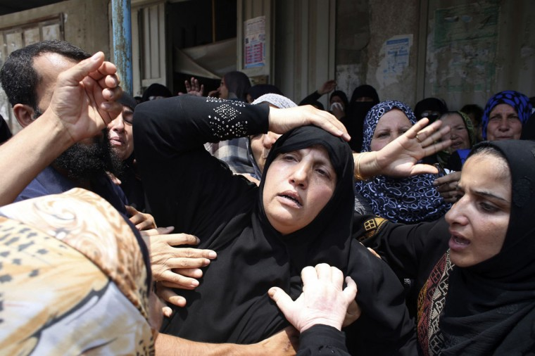 Relatives of three Palestinians from Abu Muamar family, who medics said were killed in an Israeli air strike, mourn during their funeral in Rafah in the southern Gaza Strip July 20, 2014. At least 50 Palestinians were killed on Sunday by Israeli shelling in a Gaza neighborhood, where bodies were strewn in the street and thousands fled for shelter to a hospital packed with wounded, witnesses and health officials said. Militants kept up their rocket fire on Israel, with no sign of a diplomatic breakthrough toward a ceasefire in sight. (Ibraheem Abu Mustafa/Reuters)