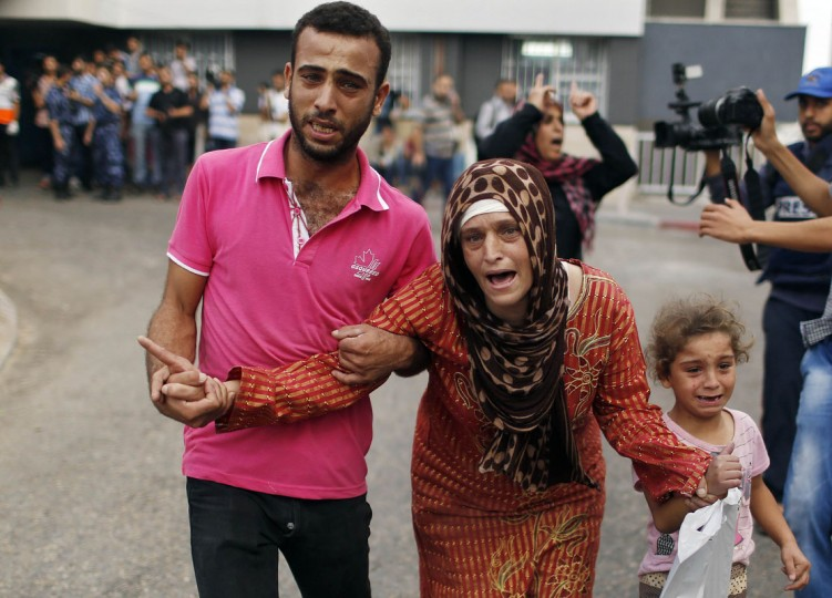 A Palestinian woman reacts after the death of her relatives, who medics said were killed during heavy Israeli shelling at the Shejaia district, at a hospital in Gaza City July 20, 2014. At least 20 Palestinians were killed on Sunday by Israeli shelling in the Gaza neighborhood, witnesses and health officials said, in what appeared to be the heaviest since Israel launched its offensive on the Palestinian territory on July 8 after cross-border rocket strikes by militants intensified. Militants kept up their rocket fire on Israel, with no sign of a diplomatic breakthrough toward a ceasefire in sight. (Suhaib Salem/Reuters)