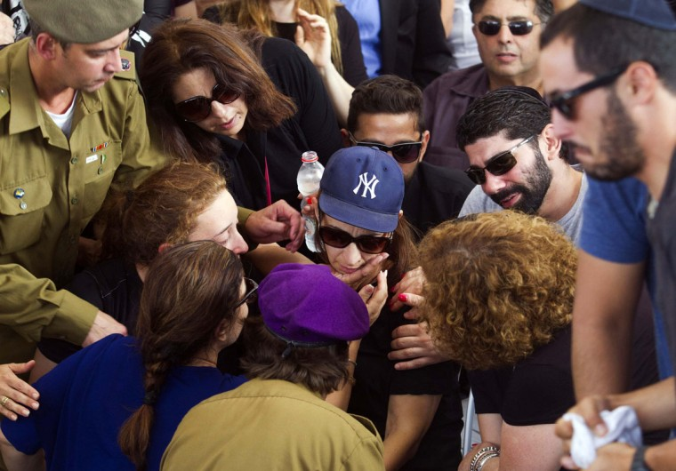 Sagit Greenberg, the wife (C, wearing cap) of Israeli soldier Amotz Greenberg, mourns during his funeral in the central town of Hod Hasharon July 20, 2014. Eighteen Israeli soldiers, including Greenberg, and two Israeli civilians have been killed since a near two-week-old offensive was launched in response, Israel says, to mounting cross-border rocket attacks by Hamas militants. Gaza's Health Ministry officials said at least 405 Palestinians, many of them civilians, have been killed and about 2,600 wounded since Israeli air and naval bombardments began on July 8, followed by a ground push on Thursday. (Tomer Appelbaum/Reuters)