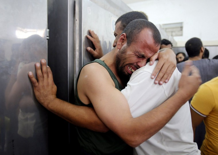 Palestinians mourn the death of their relatives, whom medics said were killed in Israeli shelling, at a hospital morgue in Rafah in the southern Gaza Strip July 21, 2014. Israeli tanks shelled militant targets in the Gaza Strip on Monday and a woman died in an air strike after the bloodiest day of a nearly two-week military offensive that showed no signs of abating, despite global calls for a truce. Palestinian health officials said the death toll since July 8 had reached 447, including many civilians, with a woman killed in the predawn strike in Beit Hanoun and 12 more bodies recovered from the embattled Shejaia neighbourhood where the number of fatalities rose to 72 from Sunday's fighting. Israel's army said it had been targeting militants from Gaza's dominant Hamas group, charging that they fired rockets from Shejaia and built tunnels and command centres there. The army said it had warned civilians to leave two days earlier. (REUTERS/Ibraheem Abu Mustafa)