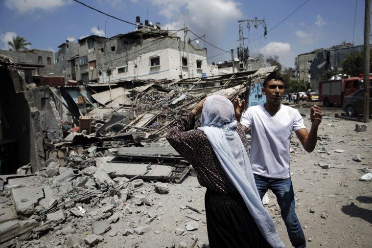 Palestinians react to destroyed homes in the Shejaia neighborhood, which was heavily shelled by Israel during fighting, in Gaza City July 20, 2014. At least 50 Palestinians were killed on Sunday by Israeli shelling in a Gaza neighborhood, where bodies were strewn in the street and thousands fled for shelter to a hospital packed with wounded, witnesses and health officials said. Militants kept up their rocket fire on Israel, with no sign of a diplomatic breakthrough toward a ceasefire in sight. (Finbarr O'Reilly/Reuters)