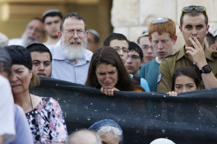 A woman mourns during a memorial service for U.S.-Israeli national Naftali Fraenkel, 16, one of three Israeli teens who were abducted and killed in the occupied West Bank, before his funeral, in the central Israeli village of Nof Ayalon July 1, 2014. Israel bombed dozens of sites in the Gaza Strip on Tuesday, striking at Hamas after finding the bodies of three missing teenagers whose abduction and killing it blames on the Palestinian Islamist group. The Islamist group has neither confirmed nor denied involvement in the disappearance of the students as they hitchhiked near a Jewish settlement on June 12 nor in the cross-border rocket salvoes from Gaza. The other two Israeli teens who were killed are Eyal Yifrah, 19, and Gil-Ad Shaar, 16. (REUTERS/Baz Ratner)