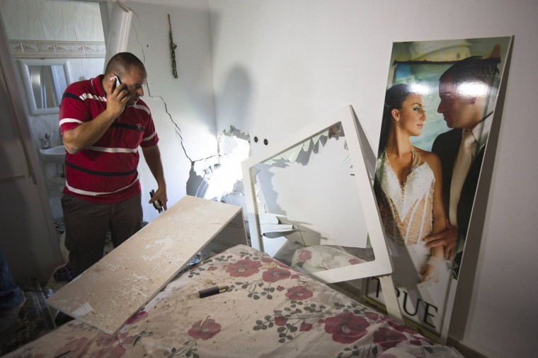 Avihai Jorno inspects the damage to his home after a rocket fired by Palestinian militants in Gaza landed in the southern town of Sderot July 3, 2014. Israeli air strikes wounded 15 people in the Gaza Strip on Thursday, local residents said, and militants kept up rocket fire on Israel, damaging two homes, in rising border tensions following the death of a Palestinian youth. (Amir Cohen/Reuters)