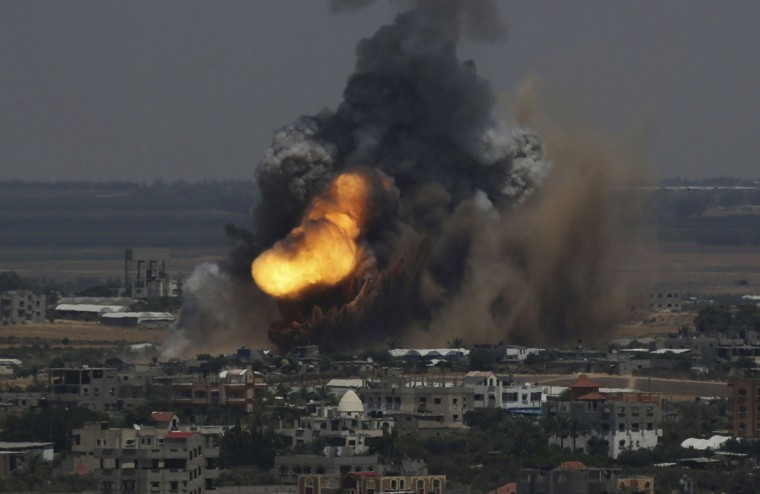 Smoke and flames are seen following what police said was an Israeli air strike in Rafah in the southern Gaza Strip July 8, 2014. Israel bombarded dozens of targets in the Gaza Strip on Tuesday, stepping up what it said might become a long-term offensive against Islamist Hamas after a surge in Palestinian rocket attacks on Israeli towns. (REUTERS/Ibraheem Abu Mustafa)