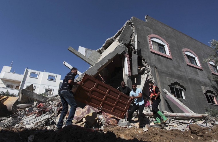 Palestinians carry a door from a destroyed house following what police said was an Israeli air strike in central Gaza Strip July 9, 2014. Israeli air strikes shook Gaza every few minutes on Wednesday, and militants kept up rocket fire at Israel's heartland in intensifying warfare that Palestinian officials said has killed at least 37 people in the Hamas-dominated enclave. REUTERS/Ashraf Amrah