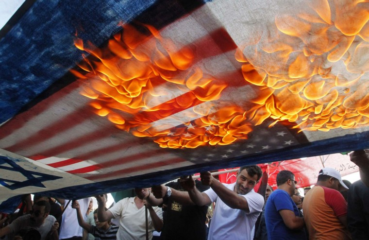 Lebanese and Palestinian protesters set fire to U.S. and Israeli flags during a demonstration to denounce Israeli air strikes on the Gaza strip, in Lebanon's southern port-city of Sidon July 10, 2014. At least 77 Palestinians, most of them civilians, have been killed in Israel's Gaza offensive, Palestinian officials said on Thursday, and militants kept up rocket attacks on Tel Aviv, Jerusalem and other cities in warfare showing no signs of ending soon. REUTERS/Ali Hashisho