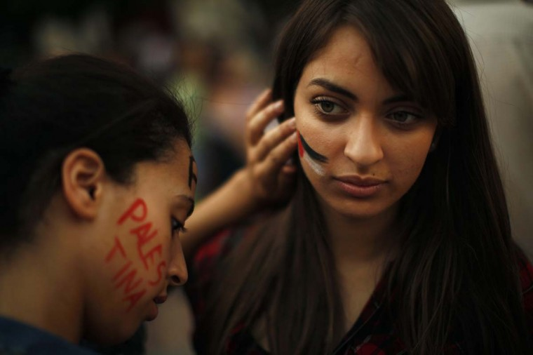 A Morrocan woman paints the Palestinian flag on the face of a compatriot during a protest against Israel's military action in Gaza, at La Constitucion square in Malaga, southern Spain, July 17. Israeli Prime Minister Benjamin Netanyahu on Thursday instructed the military to begin a ground offensive in Gaza, an official statement from his office said. The Israeli military says Gaza militants have fired more than 1,300 rockets into Israel. Palestinian health officials say 233 Palestinians have been killed in Israeli air and naval strikes.  The International Business Times today reported that the Israeli death toll during the two-week conflict stood at 2.  || PHOTO CREDIT: JON NAZCA  - REUTERS