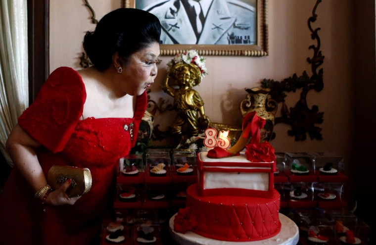 Former first lady Imelda Marcos blows a candle on a cake with a shoe decoration during her 85th birthday celebration in her husband late president Ferdinand Marcos' hometown of Batac in Ilocos Norte province, northern Philippines. (Erik De Castro/Reuters)