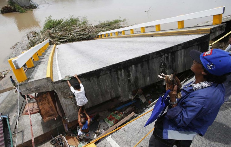 A resident climbs on a bridge destroyed during the onslaught of Typhoon Rammasun, (locally named Glenda) in Batangas city south of Manila, July 17. The Philippines set to work clearing debris, reconnecting power and rebuilding flattened houses on Thursday after a typhoon swept across the country killing 38 people, with at least eight missing, rescue officials said. Typhoon Rammasun, the strongest storm to hit the Philippines this year, was heading towards China after cutting a path across the main island of Luzon, shutting down the capital and knocking down trees and power lines, causing widespread blackouts.      || PHOTO CREDIT: ERIK DE CASTRO  - REUTERS