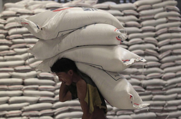 A worker carries sacks of rice while unloading inside the National Food Authority (NFA) warehouse in Taguig city, south of Manila July 3, 2014. The Philippines, one of the world's biggest rice importers, is buying an additional 200,000 tons from Vietnam, the world's No. 2 supplier after India, to stabilize local retail prices that have surged more than 20 percent from last year due to tight supply, local media reported. (Romeo Ranoco/Retuers)