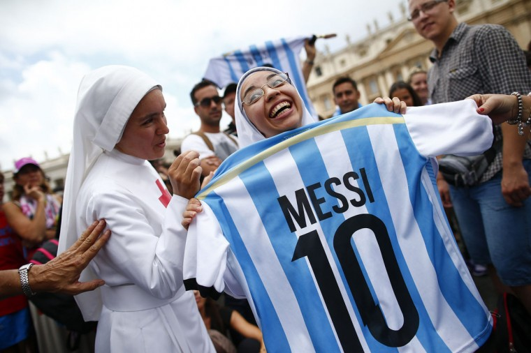 A nun holds an Argentinian national soccer team jersey as she waits for Pope Francis' Sunday Angelus prayer in Saint Peter's square at the Vatican July 13, 2014. (Tony Gentile/Reuters)