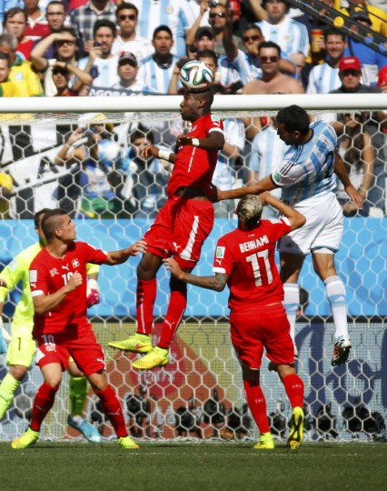 Switzerland's Johan Djourou (C) jumps for the ball with Argentina's Ezequiel Garay (R) near Switzerland's goal area during their 2014 World Cup round of 16 game at the Corinthians arena in Sao Paulo July 1, 2014. (Paul Hanna/Reuters)