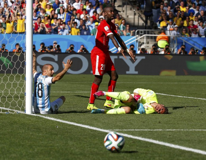 Switzerland's goalkeeper Diego Benaglio (R) lies on the pitch as teammate Johan Djourou gestures and Argentina's Rodrigo Palacio reacts during their 2014 World Cup round of 16 game at the Corinthians arena in Sao Paulo July 1, 2014. (Paul Hanna/Reuters)