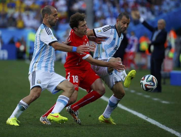 Switzerland's Admir Mehmedi (C) challenges Argentina's Javier Mascherano (R) near Pablo Zabaleta during their 2014 World Cup round of 16 game at the Corinthians arena in Sao Paulo July 1, 2014. (Paul Hanna/Reuters)