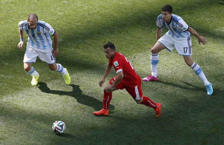 Switzerland's Xherdan Shaqiri (C) fights for the ball against Argentina's Pablo Zabaleta and Federico Fernandez (R) during their 2014 World Cup round of 16 game at the Corinthians arena in Sao Paulo July 1, 2014. (Paulo Whitaker/Reuters)