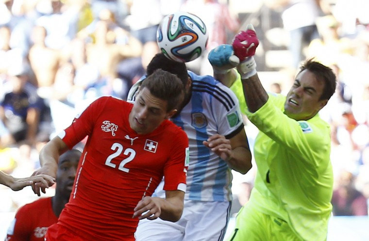 Switzerland's Fabian Schaer jumps for the ball with Argentina's Ezequiel Garay during their 2014 World Cup round of 16 game at the Corinthians arena in Sao Paulo July 1, 2014. (Kai Pfaffenbach/Reuters)