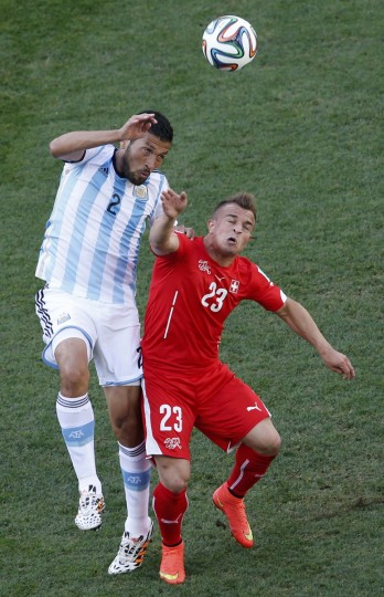 Argentina's Ezequiel Garay jumps for the ball with Switzerland's Xherdan Shaqiri (R) during their 2014 World Cup round of 16 game at the Corinthians arena in Sao Paulo July 1, 2014. (Paulo Whitaker/Reuters)