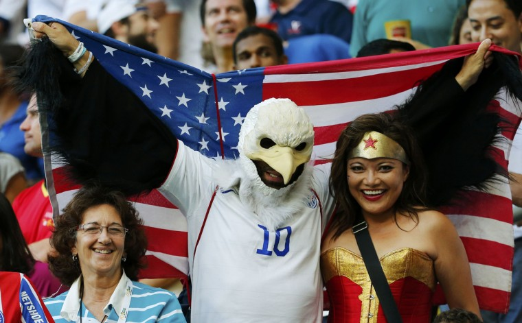 Fans of the U.S. pose for a photo with the national flag before their 2014 World Cup round of 16 game against Belgium at the Fonte Nova arena in Salvador July 1, 2014. (Yves Herman/Reuters)