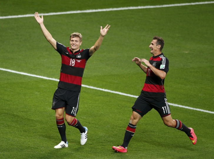 Germany's Toni Kroos (L) celebrates past his teammate Miroslav Klose after scoring his team's third goal against Brazil during their 2014 World Cup semi-finals at the Mineirao stadium in Belo Horizonte July 8, 2014. (David Gray/Reuters)