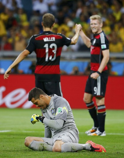 Brazil's goalkeeper Julio Cesar (front) reacts as Germany's Andre Schuerrle (R) celebrates with teammate Thomas Mueller after scoring the team's sixth goal during their 2014 World Cup semi-finals at the Mineirao stadium in Belo Horizonte July 8, 2014. (Kai Pfaffenbach/Reuters)