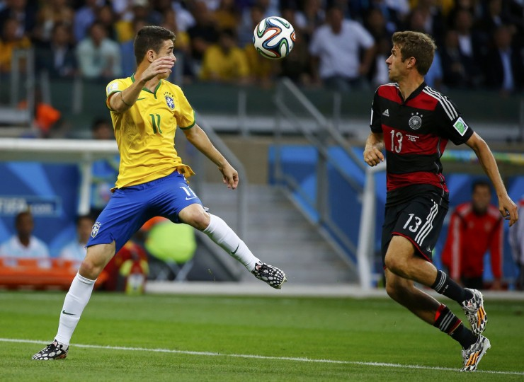 Brazil's Oscar (L) fights for the ball with Germany's Thomas Mueller during their 2014 World Cup semi-finals at the Mineirao stadium in Belo Horizonte July 8, 2014. (Damir Sagolj/Reuters)