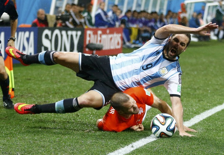 Argentina's Gonzalo Higuain (top) falls on Ron Vlaar of the Netherlands during their 2014 World Cup semi-finals at the Corinthians arena in Sao Paulo July 9, 2014. (Dominic Ebenbichler/Reuters)