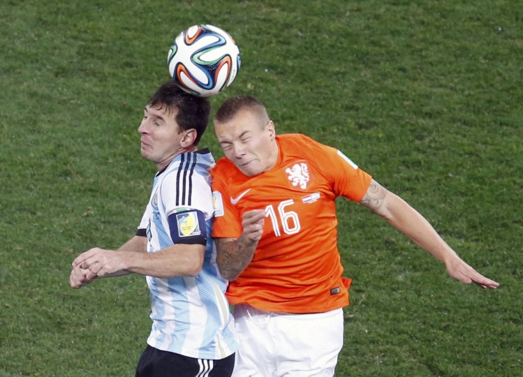 Argentina's Lionel Messi (L) and Jordy Clasie of the Netherlands reach for the ball during their 2014 World Cup semi-finals at the Corinthians arena in Sao Paulo July 9, 2014. (Paulo Whitaker/Reuters)