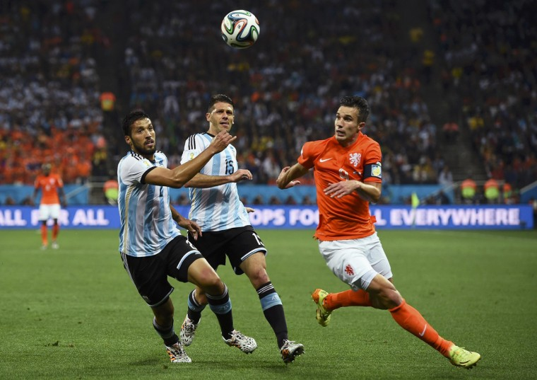 Argentina's Ezequiel Garay (L) and Martin Demichelis fight for the ball with Robin van Persie of the Netherlands (R) during their 2014 World Cup semi-finals at the Corinthians arena in Sao Paulo July 9, 2014. (Dylan Martinez/Reuters)