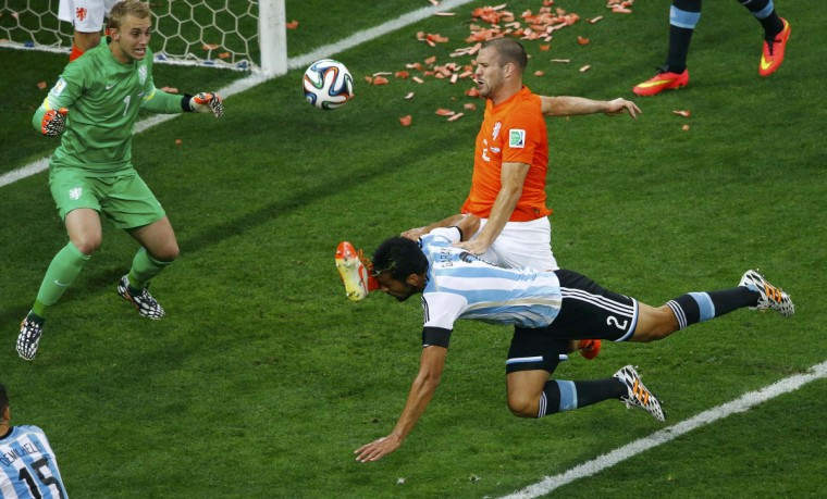 Ron Vlaar of the Netherlands fights for the ball with Argentina's Ezequiel Garay during their 2014 World Cup semi-finals at the Corinthians arena in Sao Paulo July 9, 2014. (Ricardo Moraes/Reuters)