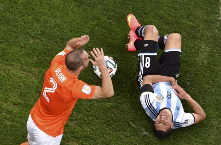 Argentina's Enzo Perez reacts after a foul by Ron Vlaar of the Netherlands (L), during their 2014 World Cup semi-finals at the Corinthians arena in Sao Paulo July 9, 2014. (Francois Xavier Marit/Reuters)