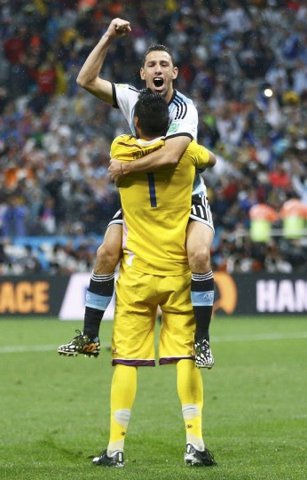 Argentina's Maxi Rodriguez (top) celebrates with goalkeeper Sergio Romero after scoring the winning penalty against Netherlands during a penalty shootout in their 2014 World Cup semi-finals at the Corinthians arena in Sao Paulo July 9, 2014. (Dominic Ebenbichler/Reuters)