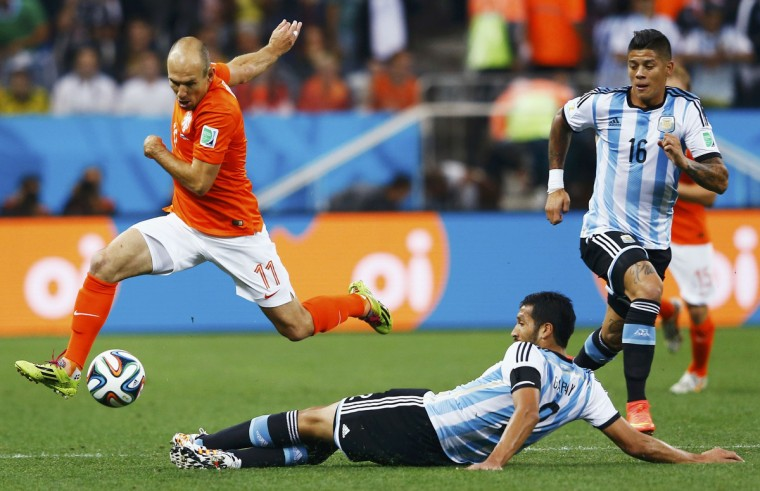 Arjen Robben of the Netherlands (L) dribbles the ball past Argentina's Ezequiel Garay and Marcos Rojo (R) during their 2014 World Cup semi-finals at the Corinthians arena in Sao Paulo July 9, 2014. (Dominic Ebenbichler/Reuters)