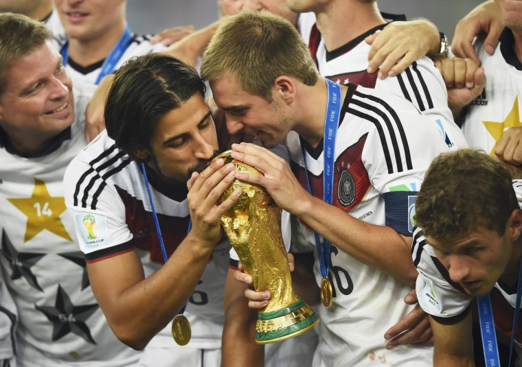 Germany's Sami Khedira (L) and Philipp Lahm (2nd R) kiss the World Cup trophy as they celebrate at the end of the 2014 World Cup final between Germany and Argentina at the Maracana stadium in Rio de Janeiro July 13, 2014. (Dylan Martinez/Reuters)