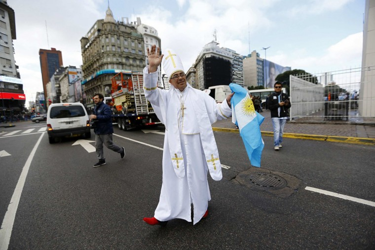 A soccer fan dressed up as Pope Francis holds up Argentina's national flag as he crosses a street, before their World Cup final soccer match against Germany, in Buenos Aires July 13, 2014. (Ivan Alvarado/Reuters)