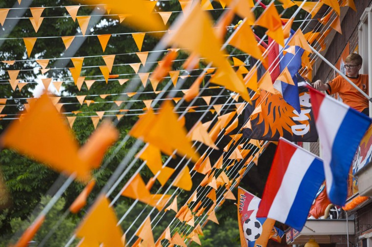 A boy decorates his house with an orange flag in Orionstraat in Amsterdam July 9, 2014. The Dutch are preparing for their semi-finals against Argentina in the 2014 World Cup in Brazil. REUTERS/Cris Toala Olivares