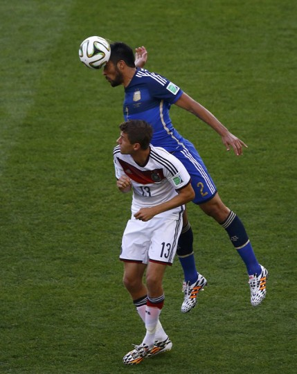 Germany's Thomas Mueller and Argentina's Ezequiel Garay (top) fight for the ball during their 2014 World Cup final at the Maracana stadium in Rio de Janeiro July 13, 2014. (Ricardo Moraes/Reuters)
